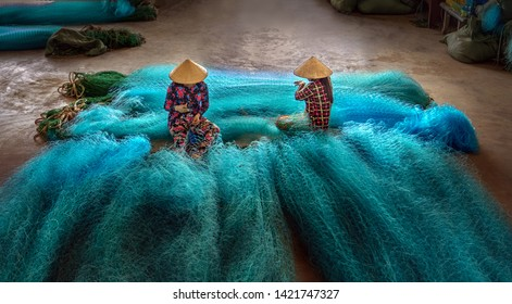 BAC LIEU CITY, VIETNAM - JULY 24 2018: Vietnamese women are sitting repairing fishing nets in a repair shop. South Vietnam