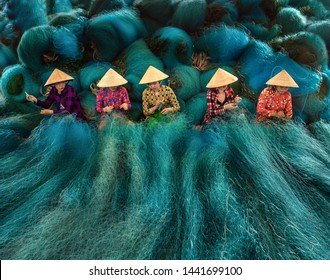 BAC LIEU CITY, VIETNAM - JULY 23 2018: Vietnamese women are sitting repairing fishing nets in a repair shop. South Vietnam