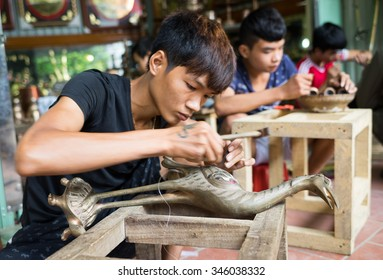 Bac Ninh, Vietnam - Sep 12, 2015: Junior craftsmen making copper handicraft products in traditional way (hand work) in Dai Bai village. Junior people are major labors in traditional works in Vietnam.