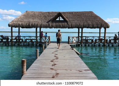 Bacalar, Mexico - 17/11/2017: Man walking on the pier of Bacalar Lake, leaving footprints