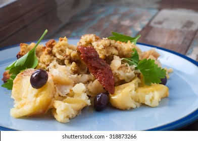 Bacalhau broa. A Portuguese Brazilian dish of salt cod baked with crumbled corn bread, olive oil and olives. Garnished with sun dried tomatoes and parsley.