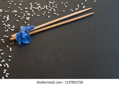 bacchette cinesi e fiori azzurri sul piano nero con i chicchi di riso bianco