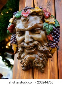 Bacchus (Dionysus) mask attached to the mulled wine stall at Christmas market in Paris (France).
