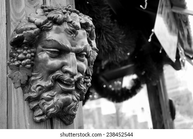 Bacchus (Dionysus) mask attached to the mulled wine stall at Christmas market in Paris (France). Aged photo. Black and white.
