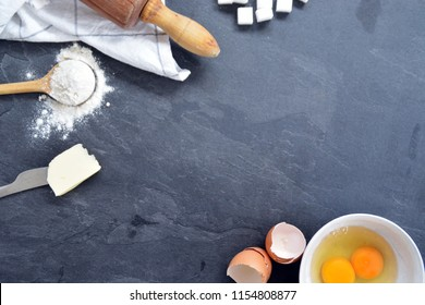 Bach utensils on a kitchen plate - eggs, flour, butter and sugar - Concept with place for text