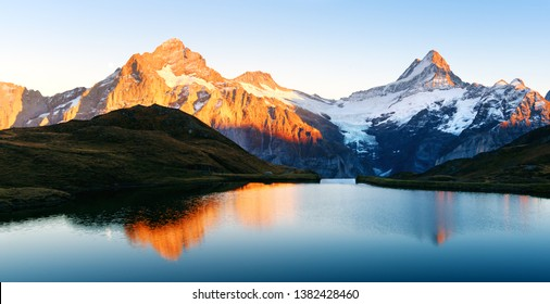 Bachalpsee lake with reflection in Swiss Alps mountains. Glowing snowy peaks on background. Grindelwald valley, Switzerland. Landscape photography - Shutterstock ID 1382428460