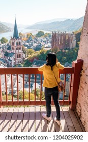 Bacharach Germany Middle Rhine Valley, young woman on the hill with wine fields looking out over the old town of Bacharach