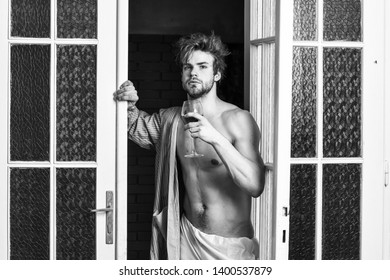 Bachelor sexy body. Sexy attractive macho tousled hair coming out through bedroom door. Man with sexy torso drink wine. Sexy lover concept. Guy smooth skin wear bathrobe. Beginning of great evening.
