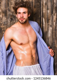 Bachelor sexy body chest and belly. Guy shimmering skin undressing bathrobe. Sexy attractive macho tousled hair on wooden background. Man athlete with fit torso. Sportsman show six pack sexy torso.