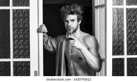 Bachelor sexy body chest and belly. Sexy attractive macho tousled hair coming out through bedroom door. Man with sexy torso drink wine. Sexy lover concept. Guy shimmering sweaty skin wear bathrobe.