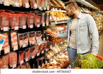 Bachelor shopping. Handsome bearded young man reading the label on a meat product while shopping at the supermarket