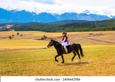Bachevo, Bulgaria - March 16, 2019: Horse Easter or the day of Todor in Bulgaria, lady in traditional bulgarian clothing riding a horse in the mountains