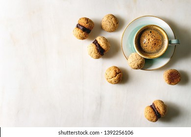 Baci di dama homemade italian hazelnut biscuits cookies with chocolate cream served in ceramic plate with cup of espresso coffee over white marble background. Flat lay, copy space