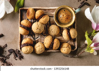 Baci di dama homemade italian hazelnut biscuits cookies with chocolate cream served in ceramic tray with cup of espresso coffee and magnolia flowers over brown texture background. Flat lay, space