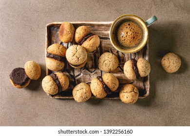 Baci di dama homemade italian hazelnut biscuits cookies with chocolate cream served in ceramic tray with cup of espresso coffee over brown texture background. Flat lay, space