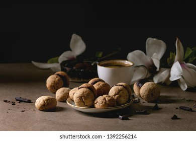 Baci di dama homemade italian hazelnut biscuits cookies with chocolate cream served in ceramic plate with cup of espresso coffee and magnolia flowers on brown table. Dark still life.