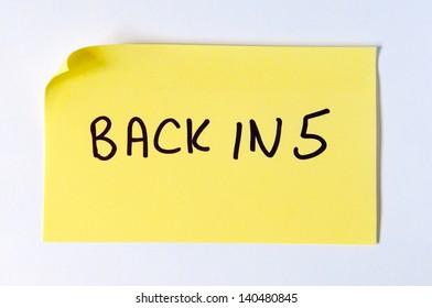 Back in 5 written on a yellow post it note