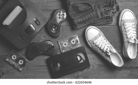 Back in the 90s. Shoes, audio tapes, video tapes, game console, jeans. Top view. Flat lat.