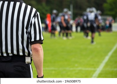 the back of an American football referee with blurred players and  field in the background