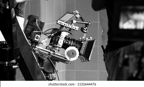 Back angle view of high definition digital video camera which recording or shooting tv commercial production on pan tilt shift professional head tripod at outdoor location and film crew team with set.