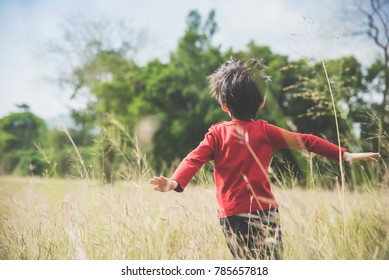 Back of  Asian child playing pilot aviator in the grass field