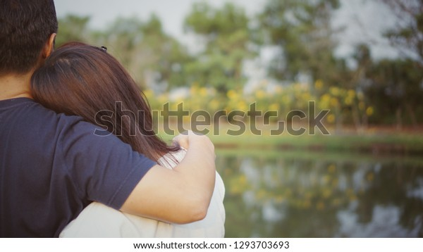 Back of Asian couple in love cuddling  and looking at the lake. Man hand hugging his girlfriend in summer day. Love, valentines, relaxation concept