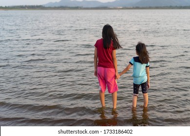Back Asian cute two child girl  Hoding hands Standing at the lake view