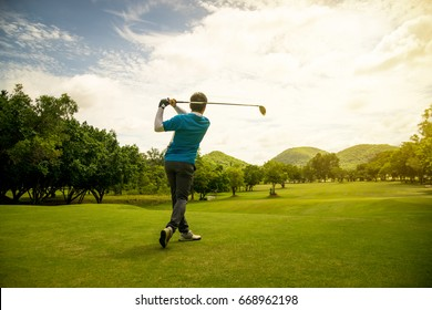 Back of Asian golfer swing golf-club driver on golf course, sunrise morning time.