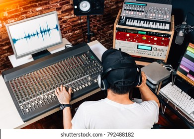 back of asian male music producer, sound engineer, composer, dj working in studio. recording, broadcasting, audio video editing concept