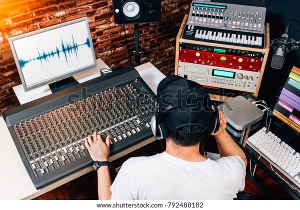 задняя часть азиатского мужского музыкального продюсера, звукорежиссер, композитор, DJ работает в студии. запись, вещание, аудио видео концепция редактирования