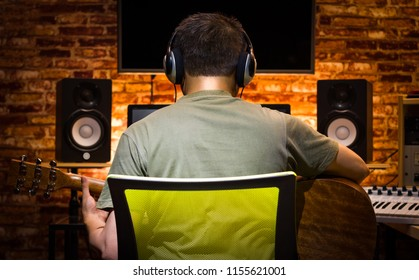 back of asian male musician recording acoustic guitar and jamming music with friends online in home studio