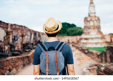 Back of Asian male solo traveller with travel hat walks inside historical buddhist ruins heritage with ancient temples in background in Ayutthaya, Thailand