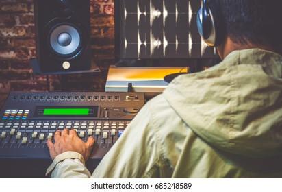back of asian sound engineer working in digital sound editing studio, DJ working in broadcasting studio, focus on hands