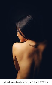 Back of Asian woman on black background
