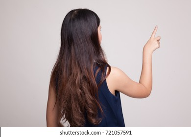 Back of Asian woman touching the screen with her finger on gray background