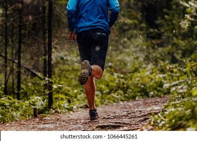 back athlete runner running under drops of rain forest trail