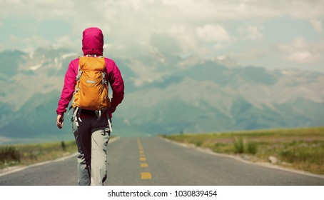 back of backpacker hiking on mountain trail
