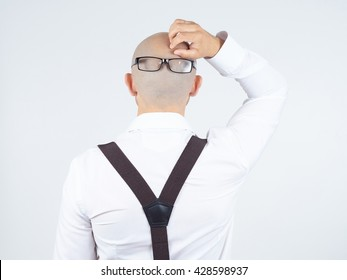 back of a bald-headed man in a white shirt with glasses on nape. scratches his head