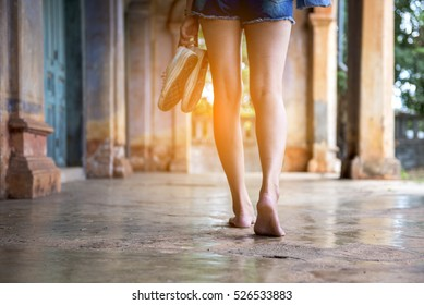 Back of barefoot, woman with shoes in hand.walking in an abandoned building