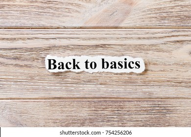 Back to Basics of the word on paper. concept. Words of Back to Basics on a wooden background.