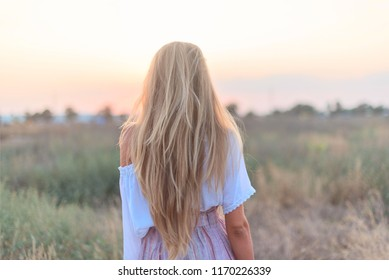 back of a beautiful blonde girl walking in a field at sunset