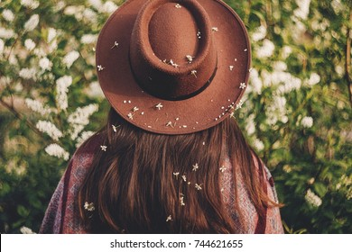 back of beautiful hipster girl in hat and poncho with amazing hair with flowers standing in park in evening sunshine. stylish woman traveler in spring garden. space for text. atmospheric moment