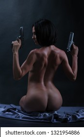 Back of beautiful naked armed woman with two pistols