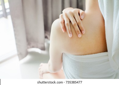back of beautiful nude asia woman with soft skin putting cream on her back.