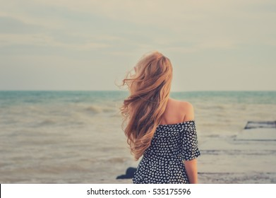 back beautiful slim girl with long flowing blond hair in the wind against the background of the sea and horizon. toned image. copy space
