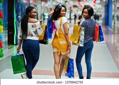 Back of beautiful three well-dressed afro american girls with colored shopping bags in mall.