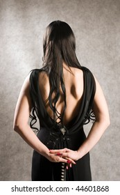 Back of the beautiful woman in a black dress and with a sword.