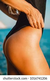 Back of beautiful woman in similar bikini on sea background. Sexy buttocks.