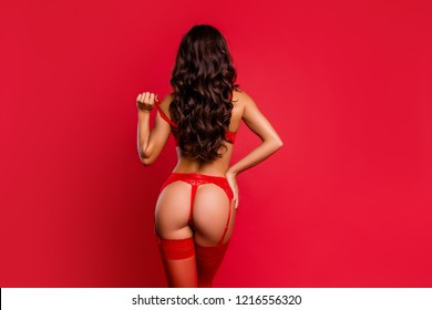 Back behind rear view alluring, magnificent, exquisite, winsome, fascinating lady in fancy lace on suspenders with wavy hairdo take off bra stand isolated on vivid red background hold hand on waist