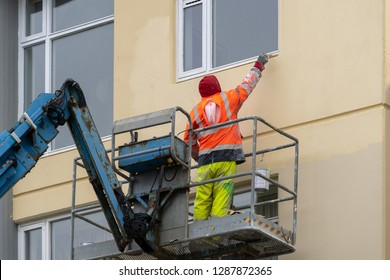 Back behind rear view photo of mature workman man with paintbrush painting multistory  building standing on mechanical scaffolding